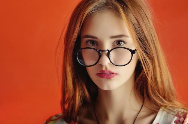 Porträt eines jungen kaukasischen weiblichen modells in gläsern in einem elfenbeinkleid auf rot