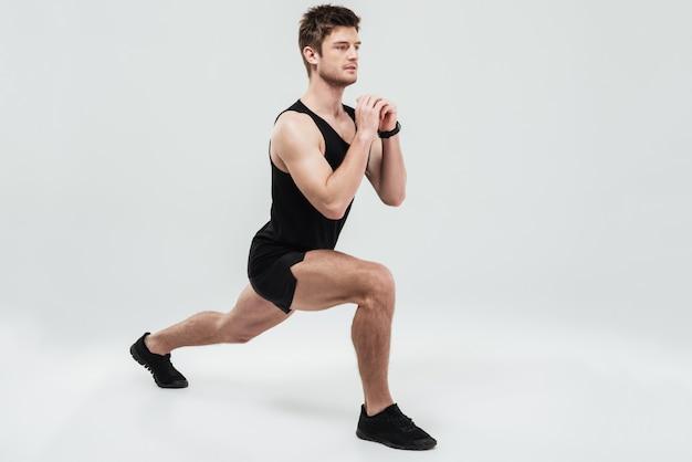 Porträt eines jungen konzentrierten mannes, der kniebeugenübung macht