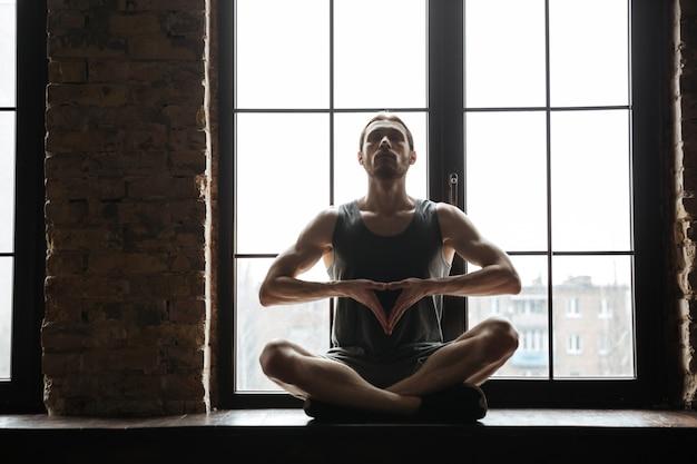 Porträt eines jungen konzentrierten sportlers, der meditiert