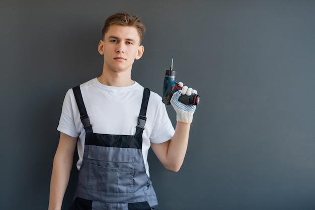 Porträt eines jungen lächelnden arbeitenden mannes in grauen overalls. arbeiter, der eine elektrische bohrmaschine auf einem grauen hintergrund hält