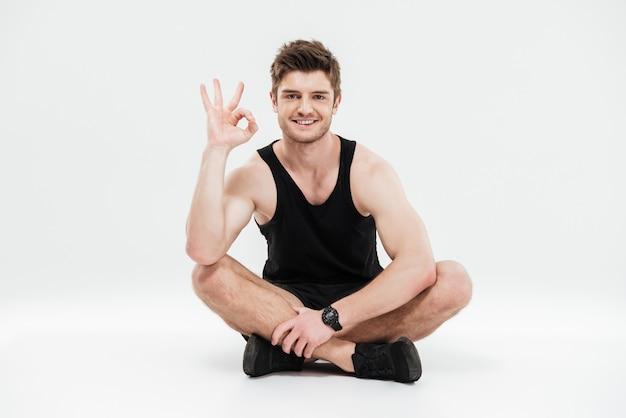 Porträt eines jungen lächelnden gesunden fitnessmanns sitzend