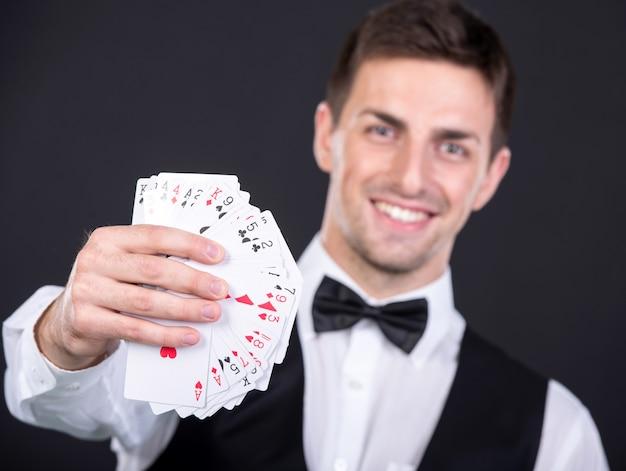 Porträt eines jungen lächelnden händlers mit spielkarten.