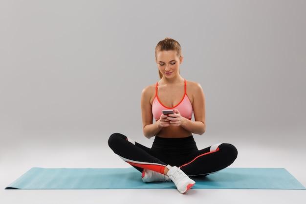 Porträt eines jungen lächelnden sportmädchens unter verwendung des mobiltelefons