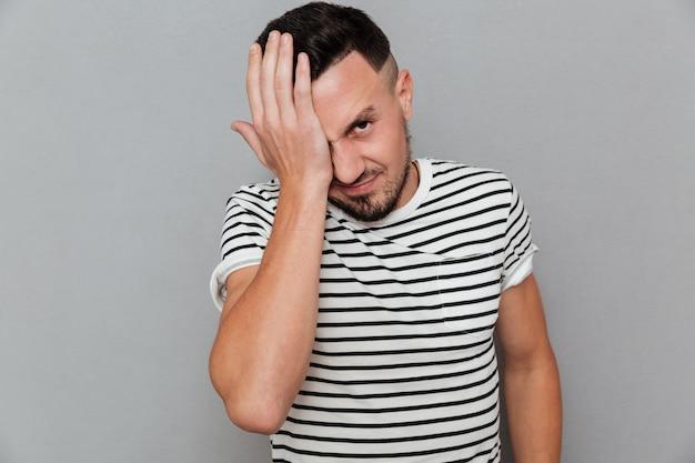 Porträt eines jungen lässigen mannes, der an einer migräne leidet