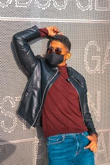 Porträt eines jungen latino-mannes, der sich an die wand lehnt. jeans, lederjacke und braune schuhe