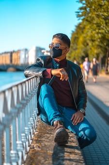 Porträt eines jungen latinos im fluss der stadt. jeans, lederjacke und braune schuhe