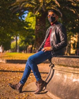 Porträt eines jungen latinos in der stadt an einem brunnen. jeans, lederjacke und braune schuhe