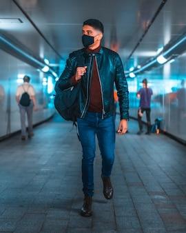 Porträt eines jungen latinos in der u-bahn der stadt. jeans, lederjacke und braune schuhe