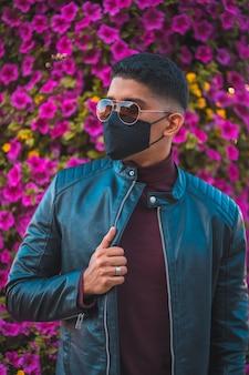 Porträt eines jungen latinos mit rosa blüten im hintergrund. jeans, lederjacke und braune schuhe