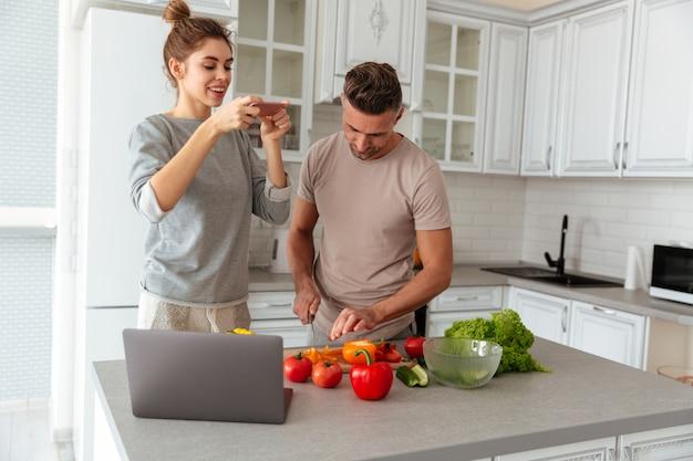 Porträt eines jungen liebevollen paares, das zusammen salat kocht