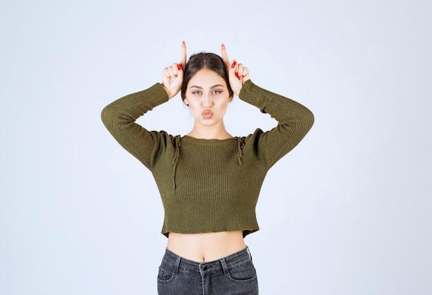 Porträt eines jungen lustigen frauenmodells, das häschenohren mit den fingern steht und zeigt.