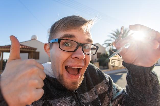 Porträt eines jungen lustigen mannes, der einen neuen hausschlüssel hält und daumen hoch neues zuhause oder wohnung gestikuliert