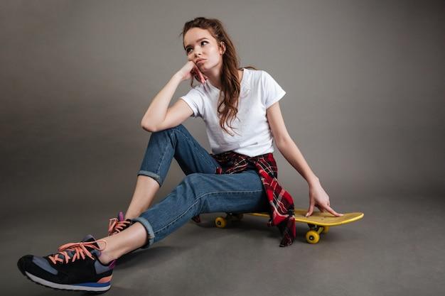 Porträt eines jungen mädchens, das auf skateboard sitzt