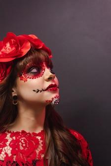 Porträt eines jungen mädchens, das mit dia de los muertos make-up oben schaut.