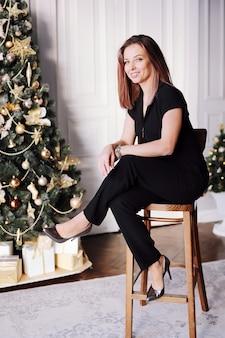Porträt eines jungen mädchens mit einem schönen lächeln, langes haar in der schwarzen kleidung nahe dem weihnachtsbaum
