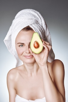 Porträt eines jungen mädchens mit gesunder und seidiger haut, wenn ein weißes tuch auf ihrem kopf eine avocadoscheibe mit einem stein hält