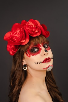 Porträt eines jungen mädchens mit make-up dia de los muertos mit grauem hintergrund.