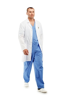 Porträt eines jungen männlichen arztes in einer medizinischen chirurgischen blauen uniform in bewegung, die den operationssaal gegen ein weiß verlässt