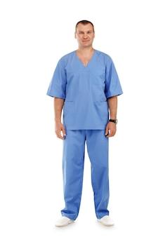 Porträt eines jungen männlichen arztes in voller länge in einer medizinischen chirurgischen blauen uniform gegen ein weißes