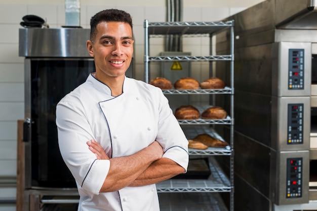 Porträt eines jungen männlichen bäckers, der mit seinen armen steht, kreuzte in seiner bäckerei