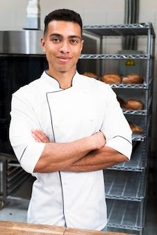 Porträt eines jungen männlichen bäckers mit seinen armen kreuzte das betrachten der kamera