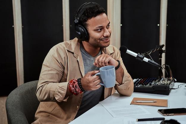 Porträt eines jungen männlichen radiomoderators, der live auf sendung geht und mit einem gast spricht, der eine tasse kaffee hält oder