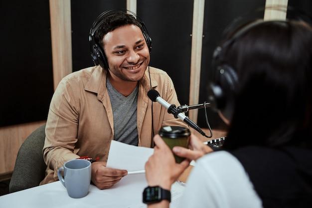 Porträt eines jungen männlichen radiomoderators, der live auf sendung geht und mit einem weiblichen gast spricht, der ein skript hält