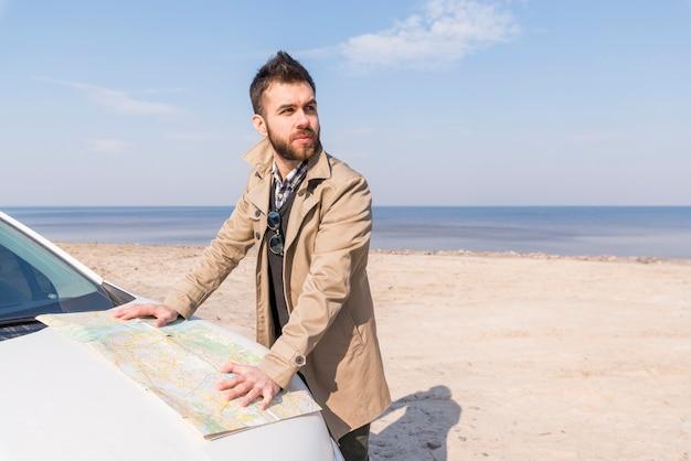 Porträt eines jungen männlichen reisenden, der auf dem strand mit karte steht