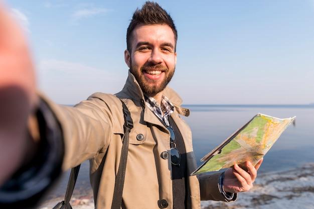 Porträt eines jungen männlichen reisenden, der in der hand die karte nimmt selfie hält
