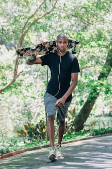 Porträt eines jungen männlichen skateboardfahrers, der skateboard auf der schulter geht in den park hält