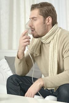 Porträt eines jungen mannes beim einatmen durch inhalatormaske