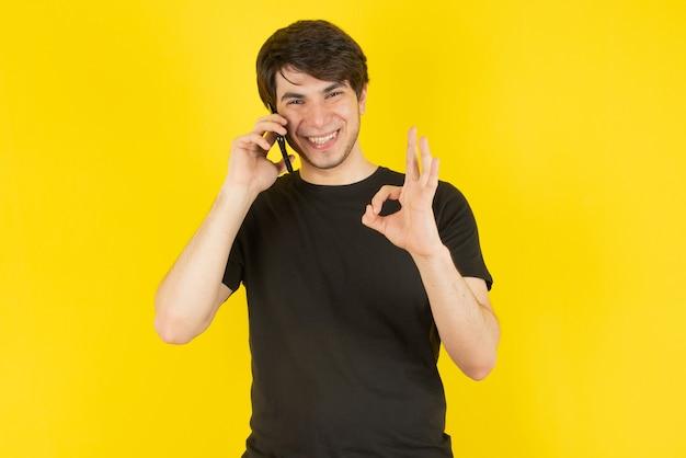 Porträt eines jungen mannes, der am handy gegen gelb spricht.