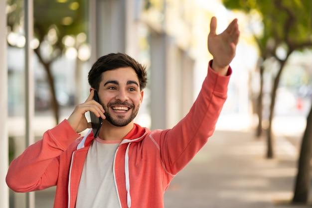 Porträt eines jungen mannes, der am telefon spricht und seine hand hebt, um ein taxi zu rufen, während er draußen auf der straße steht
