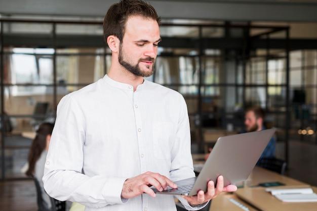 Porträt eines jungen mannes, der an laptop am arbeitsplatz arbeitet