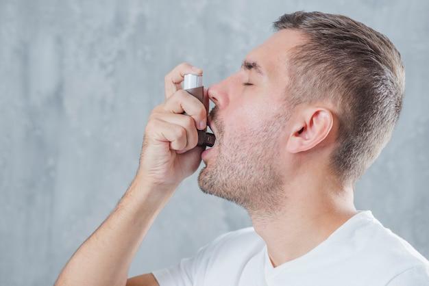 Porträt eines jungen mannes, der asthmainhalator gegen grauen hintergrund verwendet