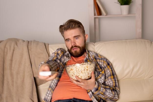 Porträt eines jungen mannes, der auf der couch sitzt und fernsieht, die fernbedienung hält und popcorn isst