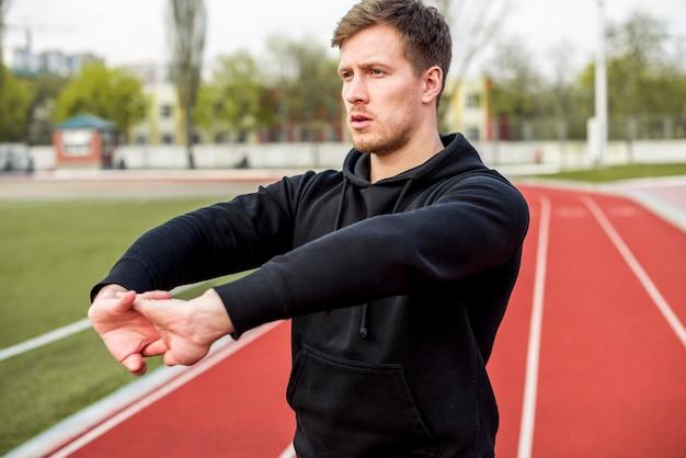 Porträt eines jungen mannes, der auf der rennstrecke ausdehnt seine hand steht