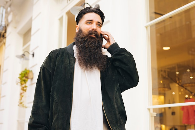Porträt eines jungen mannes, der außerhalb des shops spricht am handy steht