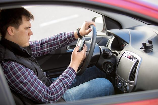 Porträt eines jungen mannes, der beim autofahren eine nachricht eingibt