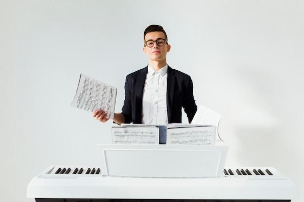 Porträt eines jungen mannes, der das musikalische blatt steht hinter dem klavier gegen weißen hintergrund hält