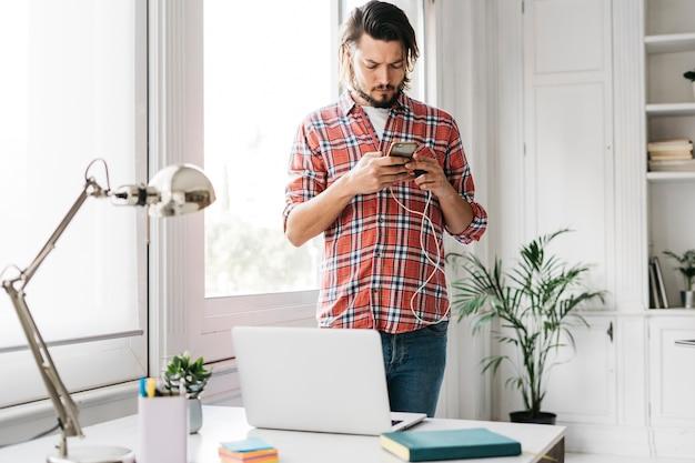 Porträt eines jungen mannes, der den handy steht nahe dem schreibtisch mit laptop verwendet