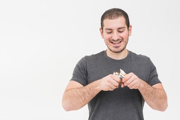 Porträt eines jungen mannes, der den haufen von den zigaretten lokalisiert auf weißem hintergrund bricht