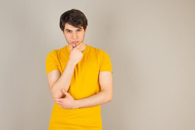 Porträt eines jungen mannes, der die kamera gegen grau steht und betrachtet.