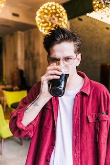 Porträt eines jungen mannes, der die kamera trinkt die biergläser betrachtet