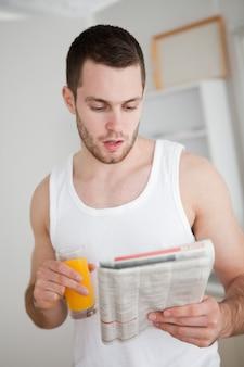 Porträt eines jungen mannes, der die nachrichten beim trinken des orangensaftes liest
