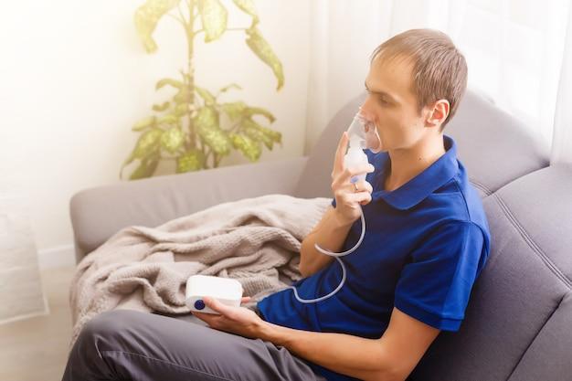 Porträt eines jungen mannes, der durch inhalatormaske einatmet