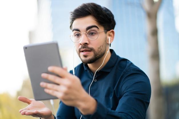 Porträt eines jungen mannes, der einen videoanruf auf einem digitalen tablet hat, während er im freien auf einer bank steht. urbanes konzept.