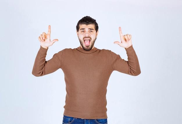 Porträt eines jungen mannes, der finger oben auf den kopienraum zeigt, der über weißem hintergrund lokalisiert wird. foto in hoher qualität