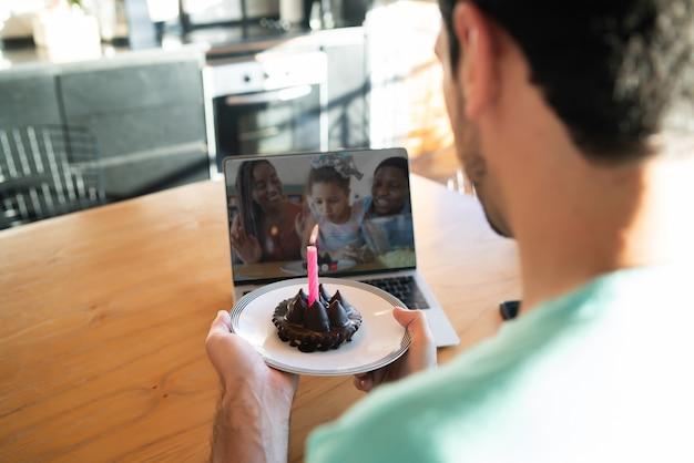 Porträt eines jungen mannes, der geburtstag bei einem videoanruf von zu hause aus mit laptop und kuchen feiert. neues normales lifestyle-konzept.