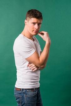 Porträt eines jungen mannes, der gegen grünen hintergrund steht
